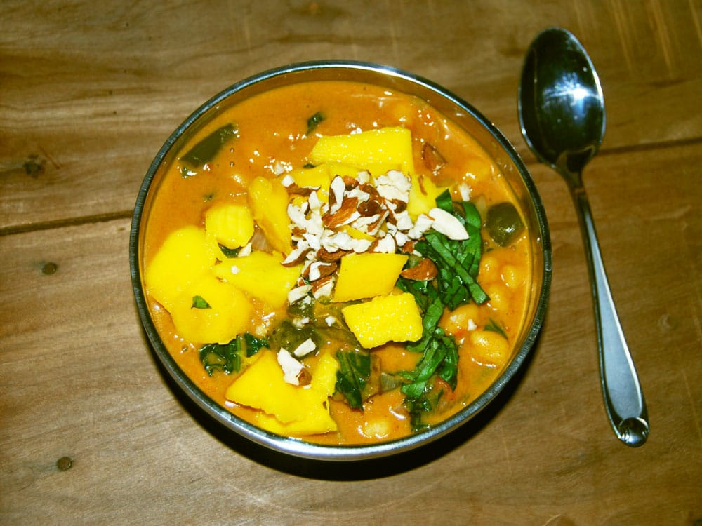 A similar curry I made in Africa and garnished with mangoes, almonds and basil!