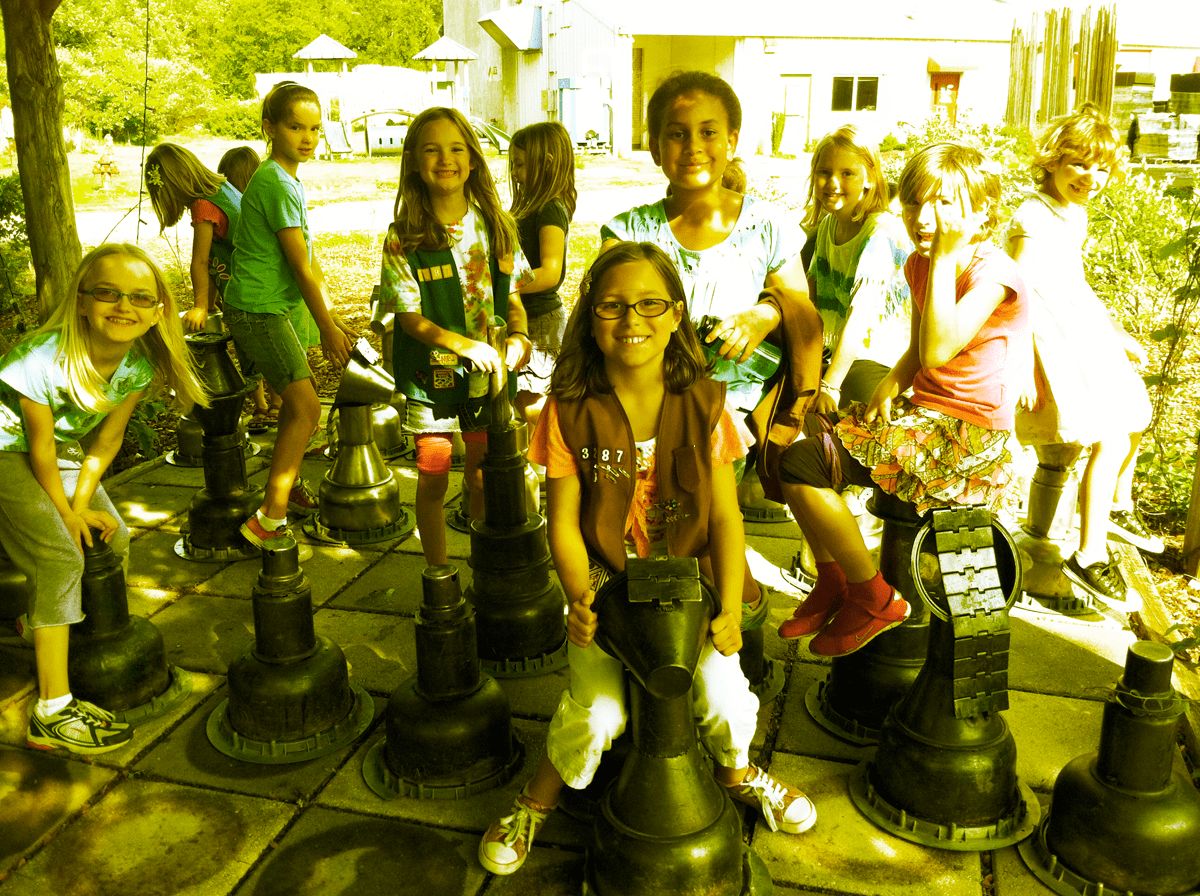 A girl scout troop on the giant chess set.