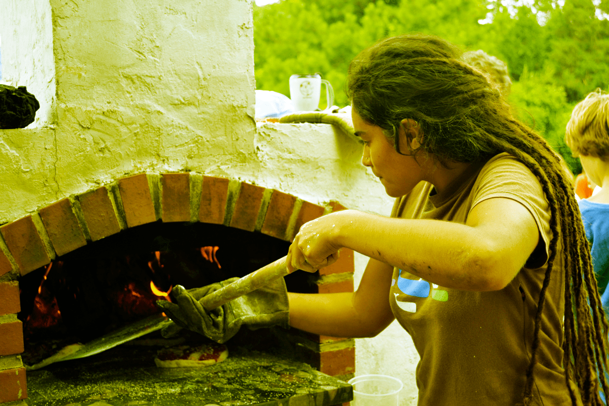 A volunteer bakes pizza in our handmade wood-oven at one of our events.
