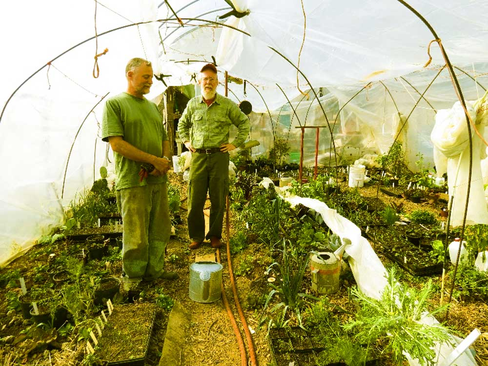 Peter Bane in a Permaculture Activist hoop house with the magazine's webmaster. Via Indiana Living Green.